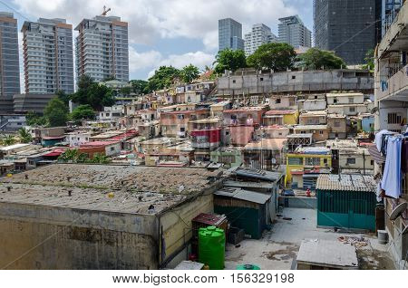 Colorful illegal houses of the poor inhabitants of Luanda Angola. These ghettos resemble Brasilian favelas. In the background the high rise buildings of the rich build a stark contrast.