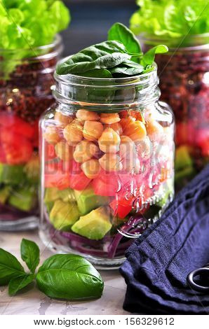 Healthy salad with quinoa and chickpeas, avocado, tomato, red onion, baby spinach, lettuce, olive oil in a Mason jars.