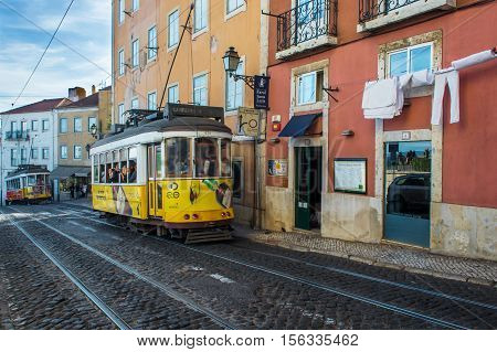 LISBON PORTUGAL - OCTOBER 13 2014. old yellow trams with tourists on the street