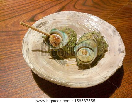 Boiled Japanese mollusk on a plate the horned turban