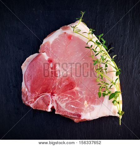 Top view raw pork chop steak t-bones on stone background.