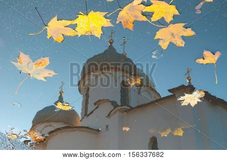 Autumn scene - reflection in a puddle of St Sophia cathedral with fallen autumn leaves in Veliky Novgorod Russia. Autumn landscape of Veliky Novgorod architecture landmark reflecting in the water