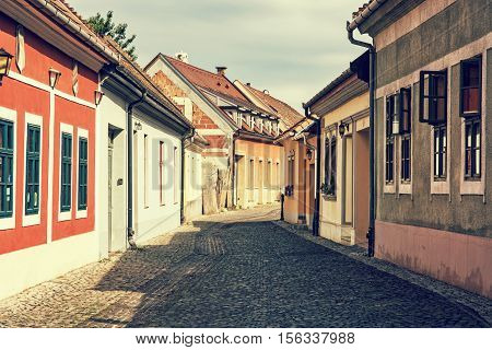 Beautiful street with old buildings in Esztergom Hungary. Cultural heritage. Architectural theme. Urban scene. Retro photo filter. Travel destination.