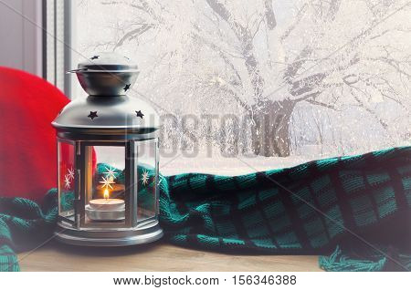 Winter background-lantern with candle and plaid with pillow on windowsill and winter scene outdoors. Winter still life with winter concept -winter background. Winter evening with cold winter outdoors