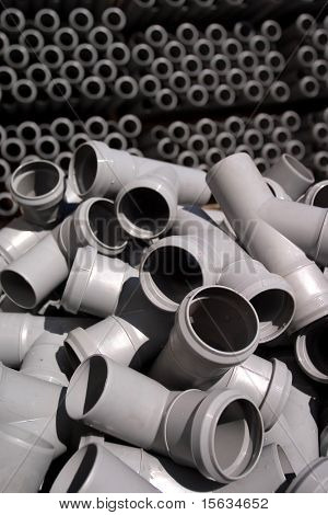 gray pvc pipes stacked in construction site