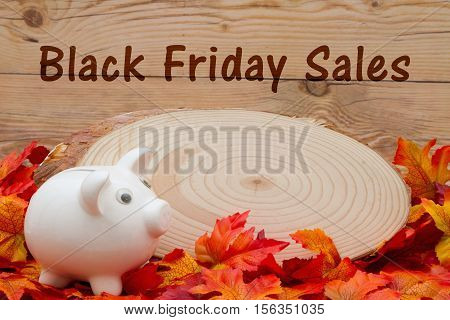 Black Friday sales message Some fall leaves with cut wood plaque and an piggy bank on weathered wood with text Black Friday Sales