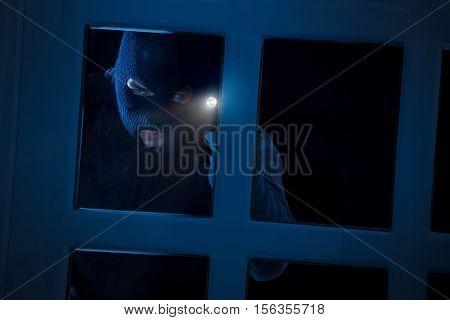Burglar with flashlight looking through the window