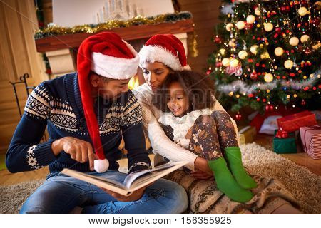 Handsome young dad reading a book to his cute daughter near Christmas tree indoor, Merry Christmas and Happy Holiday