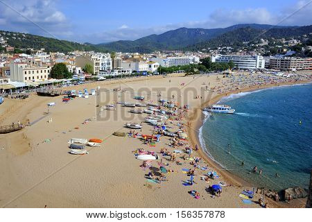 Tossa De Mar, Spain - August 1, 2014: Beach goers on the Tossa de Mar's beach