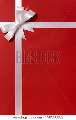 White Ribbon Bow, Red Gift Wrap Paper Background, Copy Space, Vertical