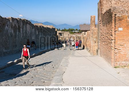 Pompeii Italy - August 29 2016: Tourists visit ruins of the ancient Roman city destroyed during a catastrophic eruption of the volcano Mount Vesuvius in 79 AD