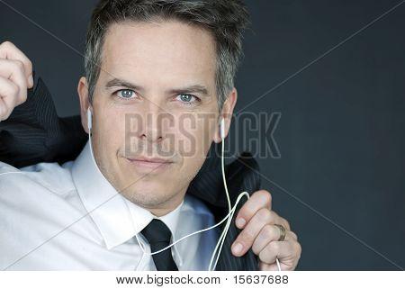 Businessman Wearing Headphones Puts On Suit Jacket