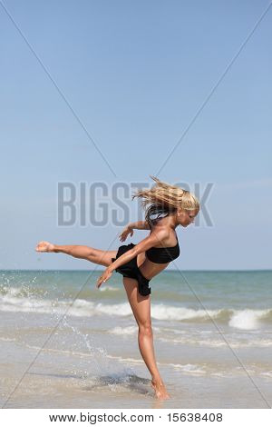 beautiful dancer posing on the sandy sea beach