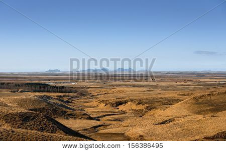 Grassland and slopes at Iceland with mountains afar