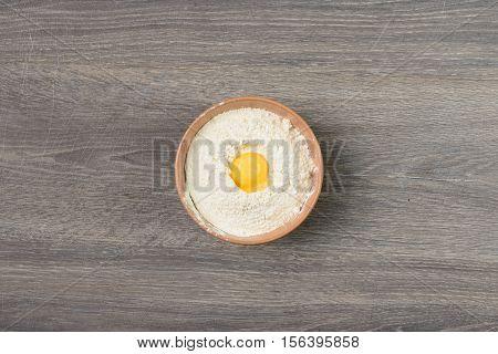Egg yolk in center of round dish full of flour