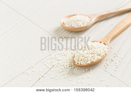 white sesame seeds on wooden spoon,Healthy Food White on the wooden floor,A mixture of food grains on a wooden spoon