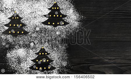 Cristmas card. On dark wooden background Christmas tree made of icing sugar flour. White Christmas Forest firs. Top view blank space