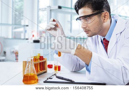 Young chemist makes chemical test by using chemical liquid in the laboratory