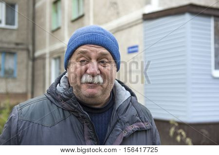 Mustachioed man in a knitted cap. Street Photography.