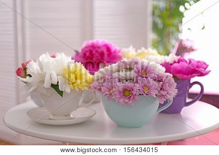 Bouquets of flower in cup on table