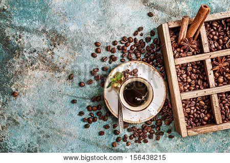 coffee beans in old wooden box, and ceramic cup of fresh making coffee over blue stone background. top view