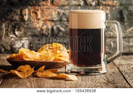 The beer style. Glass of dark beer and potato chips over wooden table on the brick wall background