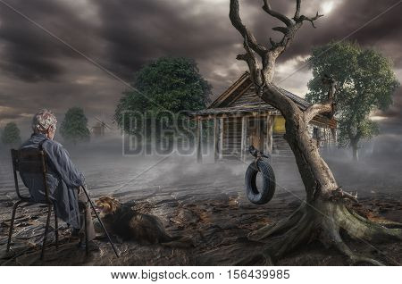 an elderly gray-haired man sits near a dry tree on the spot where was the house of his childhood