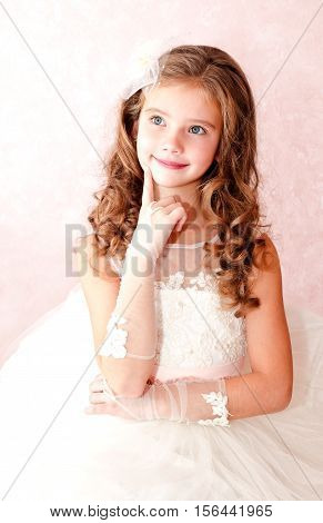 Adorable smiling little girl is dreaming in white princess dress isolated