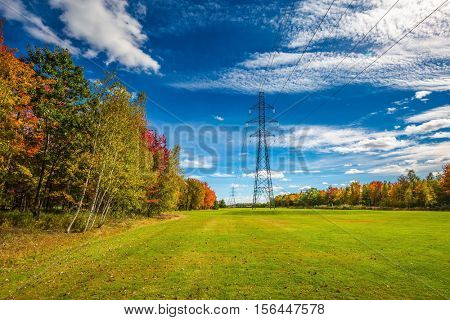 Red and green autumn foliage. Electricity transmission air-line support. Shining sunny day in French Canada