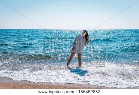 beautiful greek young brunet woman  walking on a beach in white dress