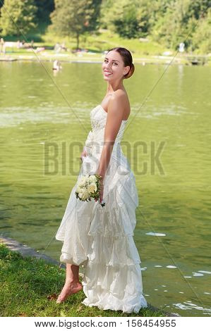 Young bride barefoot in wedding dress and bridal bouquet in hand at lake