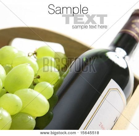 Bottle of red wine next to white grape (easy to remove the text)