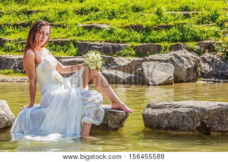 The young bride in the Wet dress sits in the lake on a stone the bridal bouquet of white roses in the hand - Landscape