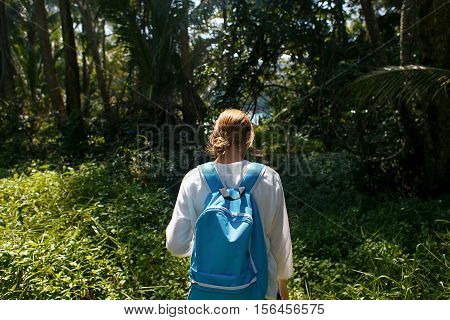 Back view of young woman with backpack outdoors discovering jungle