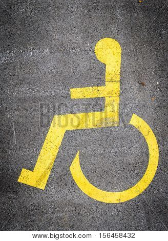 Wheelchair symbol in a Parking Lot marks disabled parking space. White iconon a blue metal square sign.