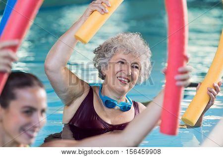 Smiling senior woman doing aqua fitness with swim noodles. Happy mature healthy woman taking fitness classes in aqua aerobics. Healthy old woman holding swim noodles doing aqua gym with young trainer.
