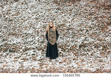 Young woman in black dress holding big oval mirror. Outdoor shot. Winter, snowy weather. Mystic gloomy gothic style