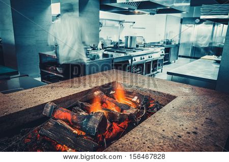 Restaurant kitchen interior: brazier with burning wood, made of natural stone with fire for BBQ. In the background buzzing restaurant work motion chefs