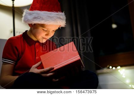 Child Opening Gift Box From Santa Claus.