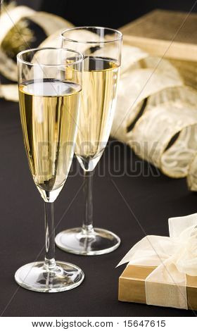 Two champagne flutes, elegant gold gift box with white ribbon. Big gold present and transparent ribbon in background. All on matt black.