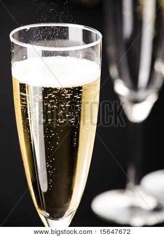 Two flutes and of champagne on matt black background.