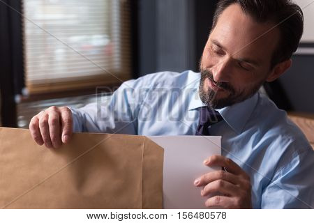 Paper work. Happy handsome diligent man holding an envelope and looking at the documents while taking them out of it