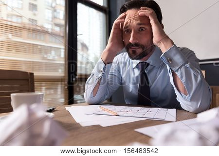 Dealing with some problems. Cheerless depressed bearded man sitting at the table and holding his head while trying to solve the problem