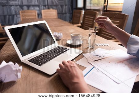 Taking medicine. Close up of a typical modern workplace with a hand of a man dissolving a pill in the glass of water