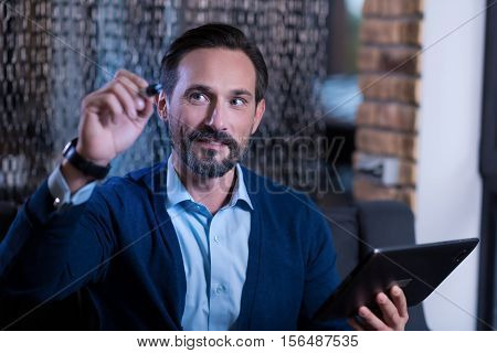 Technology era. Nice positive bearded man holding a tablet and looking at the virtual screen while writing something in it