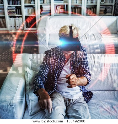 Composite image of face against senior man wearing virtual reality headset in living room