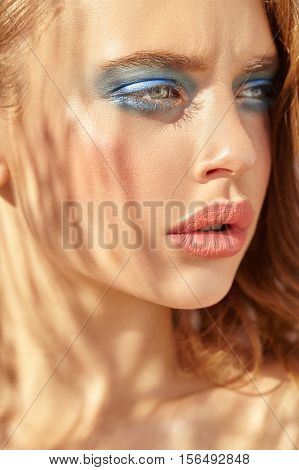 Close-up portrait of attractive girl with bright blue shadows on the eyes. Blue background.