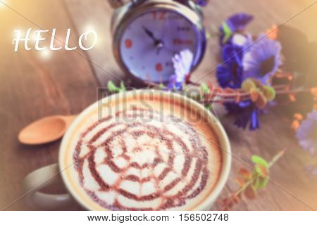 sweet dreamy and de-focused HELLO word on vintage background coffee latte art and watch on wooden table