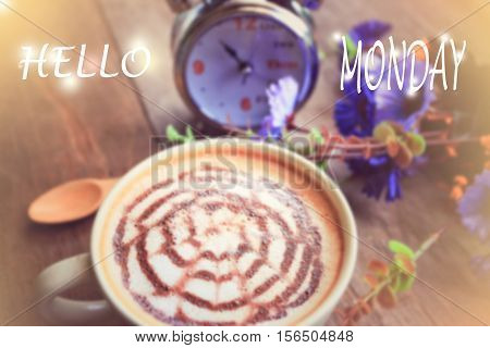 sweet dreamy and de-focused HELLO MONDAY word on vintage background coffee latte art and watch on wooden table