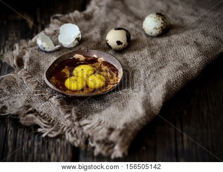 Quail egg yolks in a white plate on a wooden background
